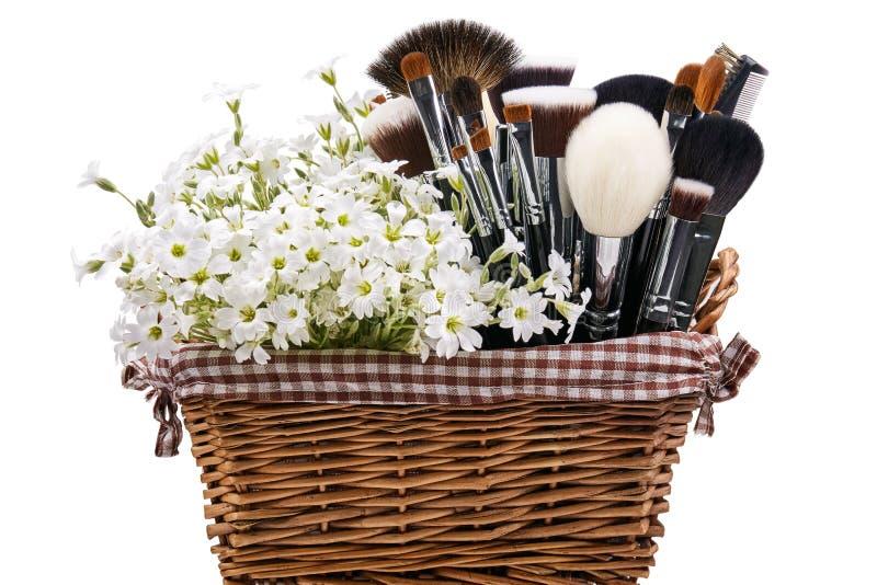 Makeupborsteuppsättning i lathund med blommor chickweed isolerat Wh arkivbilder