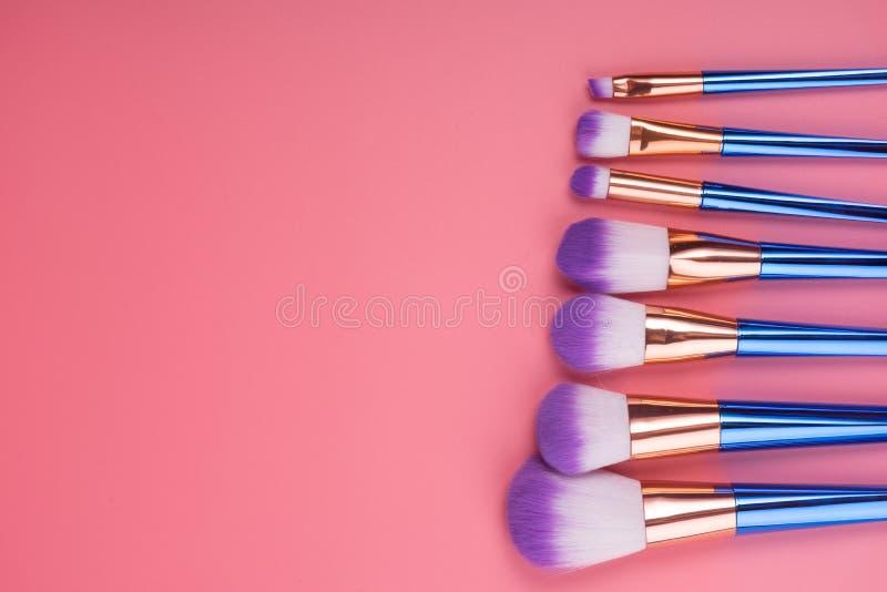Makeupborsteuppsättning på röd rosa pastellfärgad bakgrund fotografering för bildbyråer