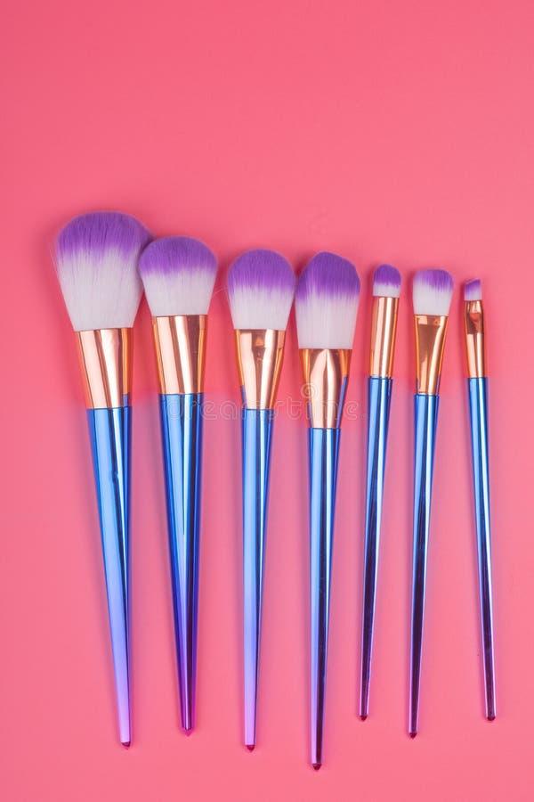 Makeupborsteuppsättning på röd rosa pastellfärgad bakgrund royaltyfri fotografi