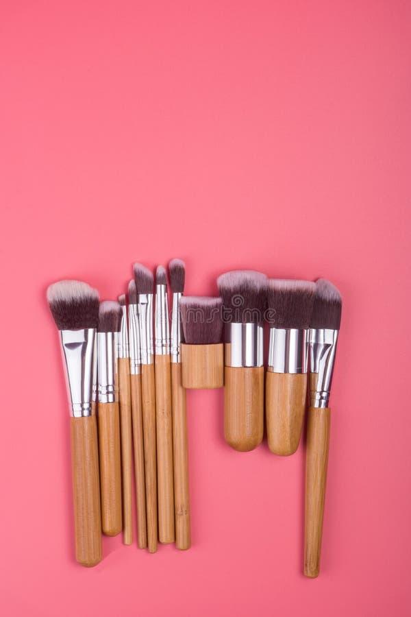 Makeupborsteuppsättning på röd rosa pastellfärgad bakgrund royaltyfri bild