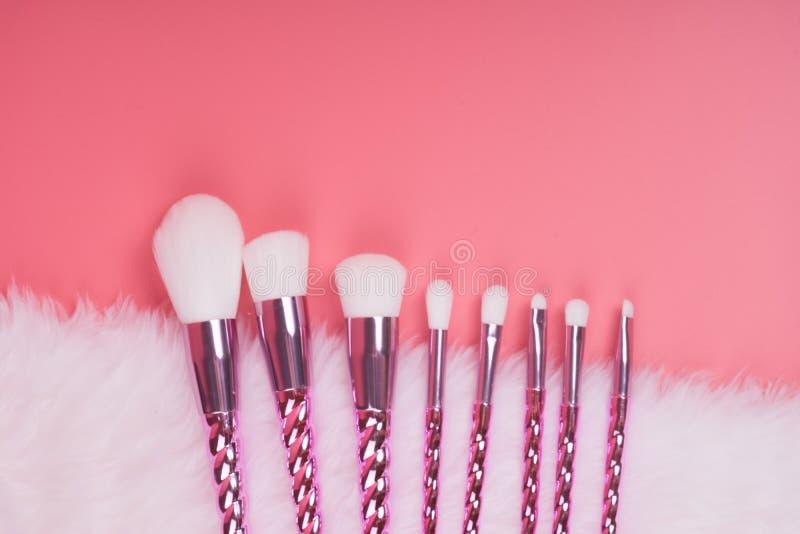 Makeupborsteuppsättning på röd rosa pastellfärgad bakgrund arkivfoto