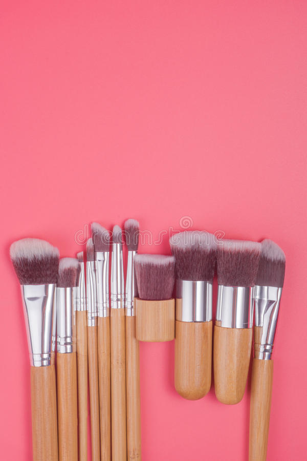 Makeupborsteuppsättning på röd rosa pastellfärgad bakgrund arkivbilder