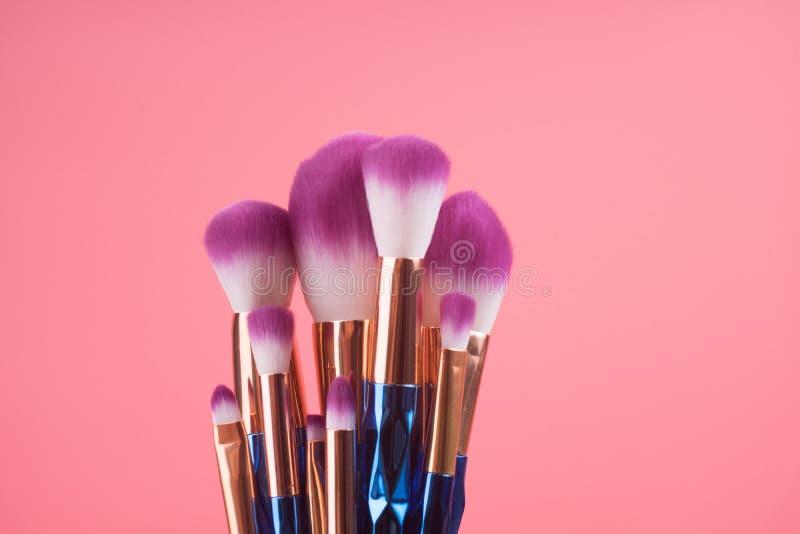 Makeupborsteuppsättning på röd rosa pastellfärgad bakgrund arkivbild