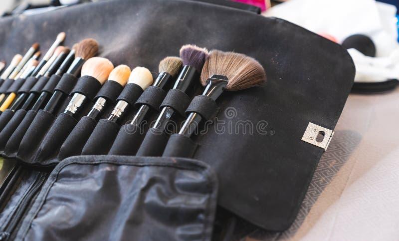 Makeupborsteuppsättning på svart tygpåse arkivbild
