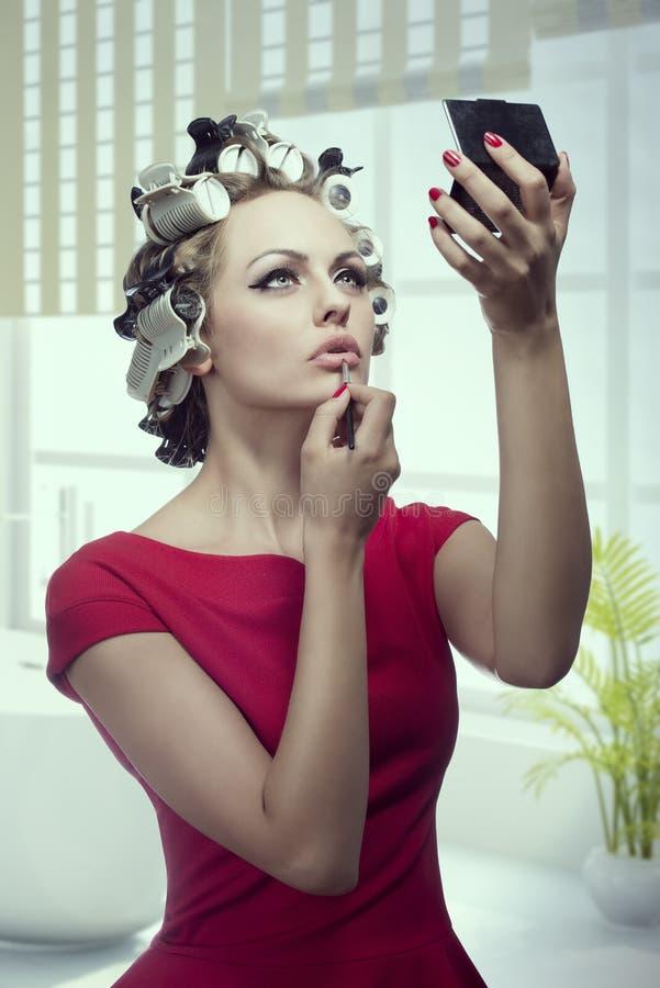 Makeupflicka med hårrullar arkivbilder