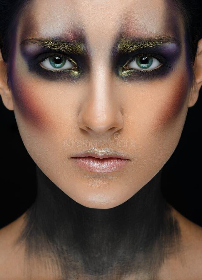 Makeupkonst och härligt modelltema: den härliga flickan med idérik sminksvart-och-lilor och guld färgar på en svart backgroun fotografering för bildbyråer