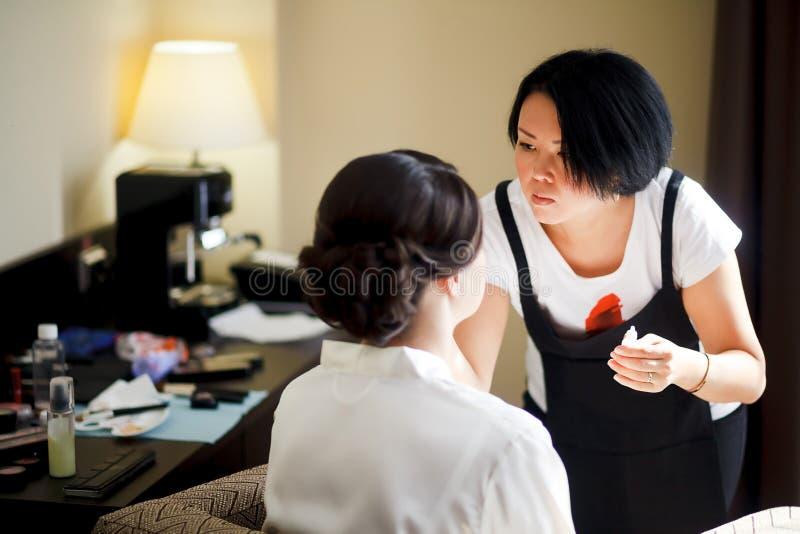 Makeupkonstnär på arbete, asiatisk kvinna som gör makeup för brud, i morgon Bröllopsklänning och skor arkivfoton