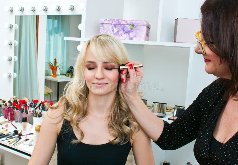 Makeupkonstnär på arbete i salong royaltyfria bilder