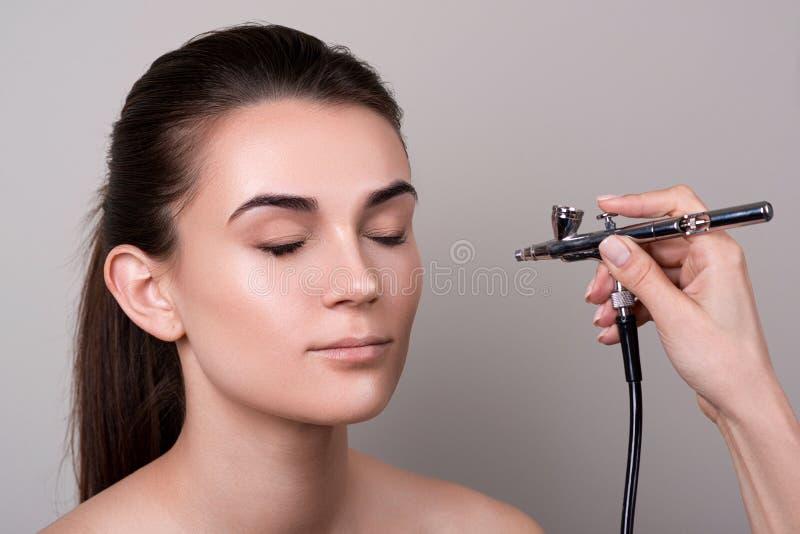 Makeupkonstnär som använder retuschsprutan Modebrunettmodell med hårsvansen över grå bakgrund Yrkesmässig makeup med aerographen  royaltyfri bild