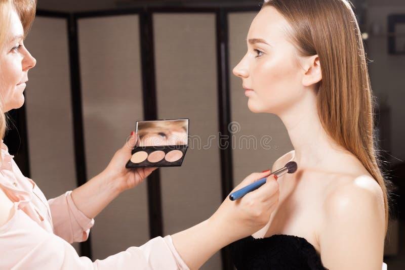 Makeupkonstnär som applicerar en täckstift på ett nyckelben av en flicka arkivfoto