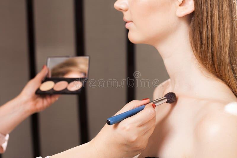 Makeupkonstnär som applicerar en täckstift på ett nyckelben av en modell arkivbilder