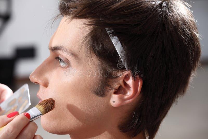 Makeupkonstnär som applicerar fundamentet med en borste, man i klänningen arkivbild