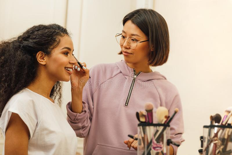 Makeupkonstnär som applicerar makeoveren på en modellframsida arkivfoton