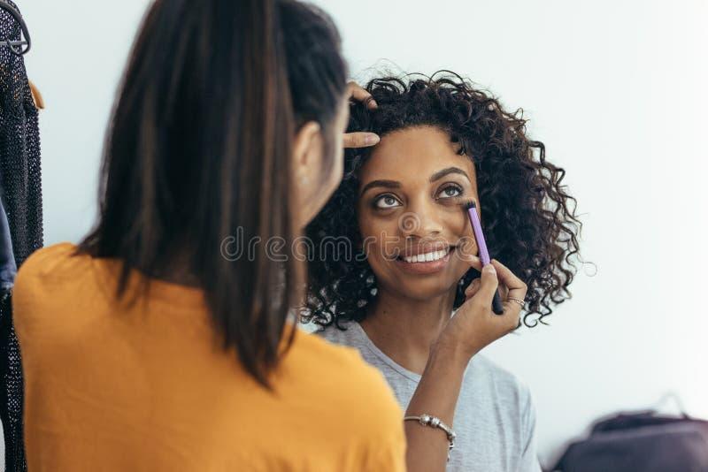 Makeupkonstnär som applicerar makeup under ögat av en modell arkivfoton