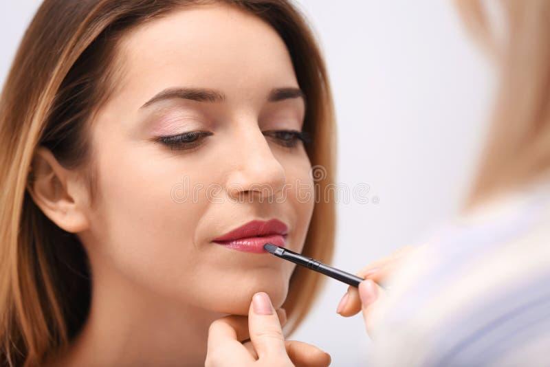 Makeupkonstnär som arbetar med den härliga modellen, royaltyfri foto