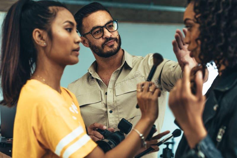Makeupkonstnär som arbetar på en modell för fotofors arkivbilder
