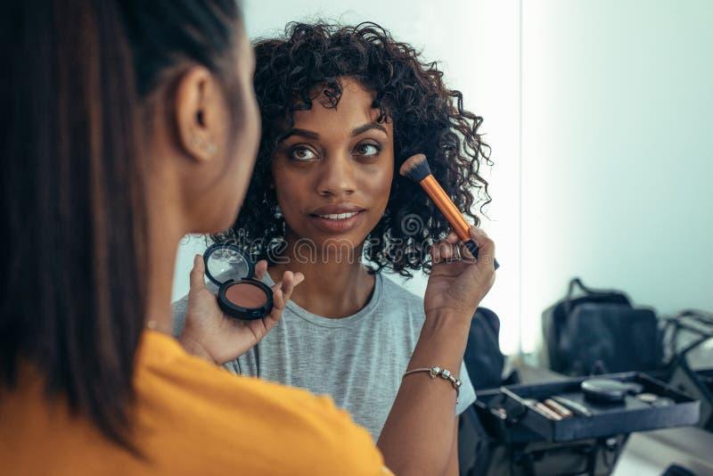 Makeupkonstnär som arbetar på framsida av en modell royaltyfria bilder