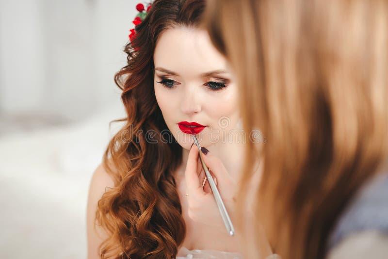 Makeupkonstnär som förbereder bruden för bröllopet arkivfoto