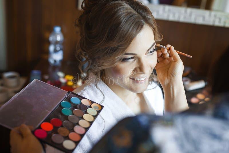 Makeupkonstnär som förbereder bruden för bröllopet i en morgon arkivbilder