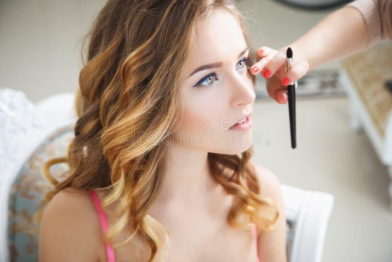 Makeupkonstnär som förbereder bruden för bröllopet i en morgon royaltyfri bild