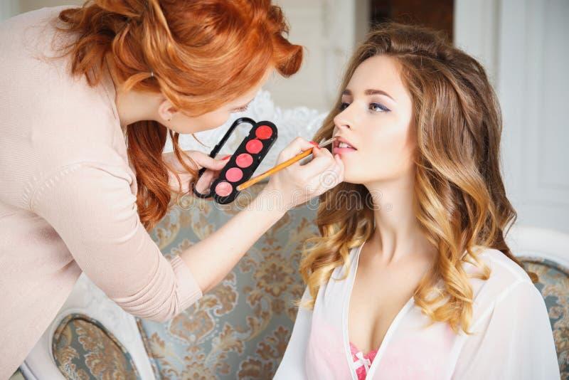 Makeupkonstnär som förbereder bruden för bröllopet i en morgon arkivfoton