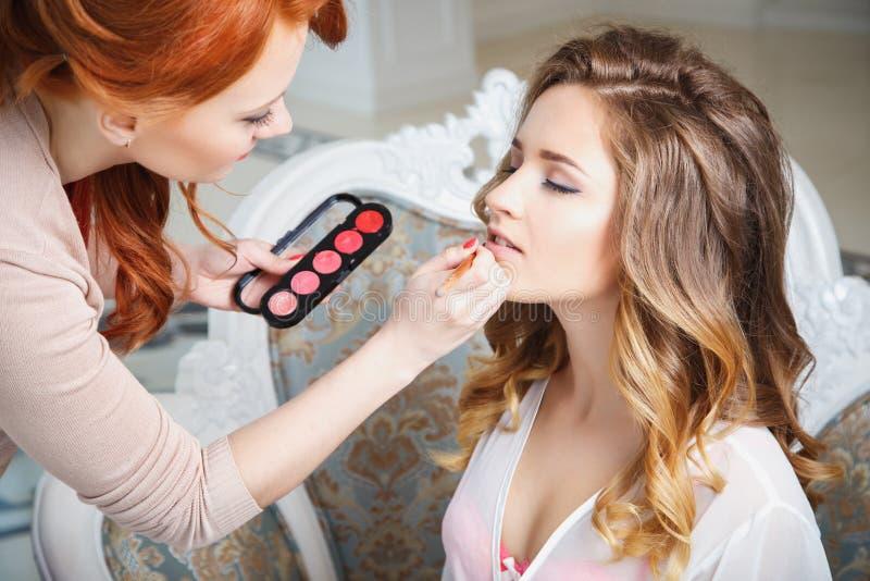 Makeupkonstnär som förbereder bruden för bröllopet i en morgon arkivbild