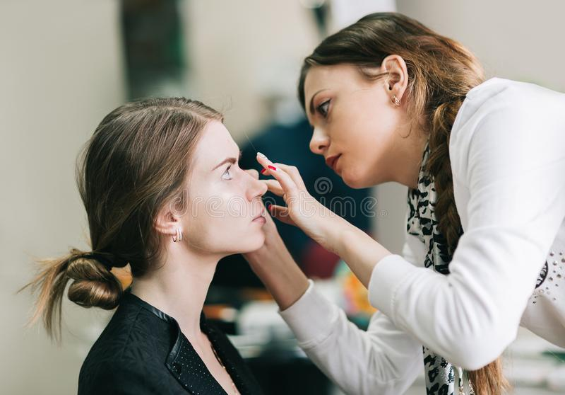 Makeupkonstnär som förbereder bruden för bröllopet i en morgon arkivfoto