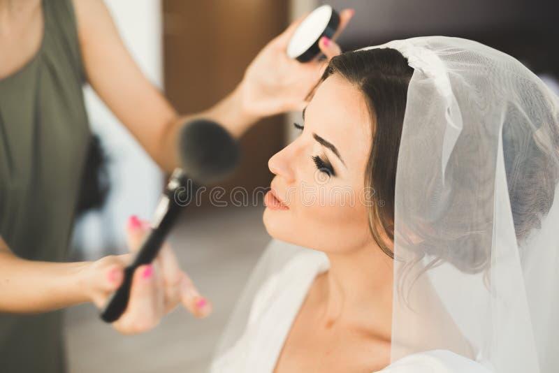 Makeupkonstnär som förbereder bruden till bröllopet royaltyfri fotografi