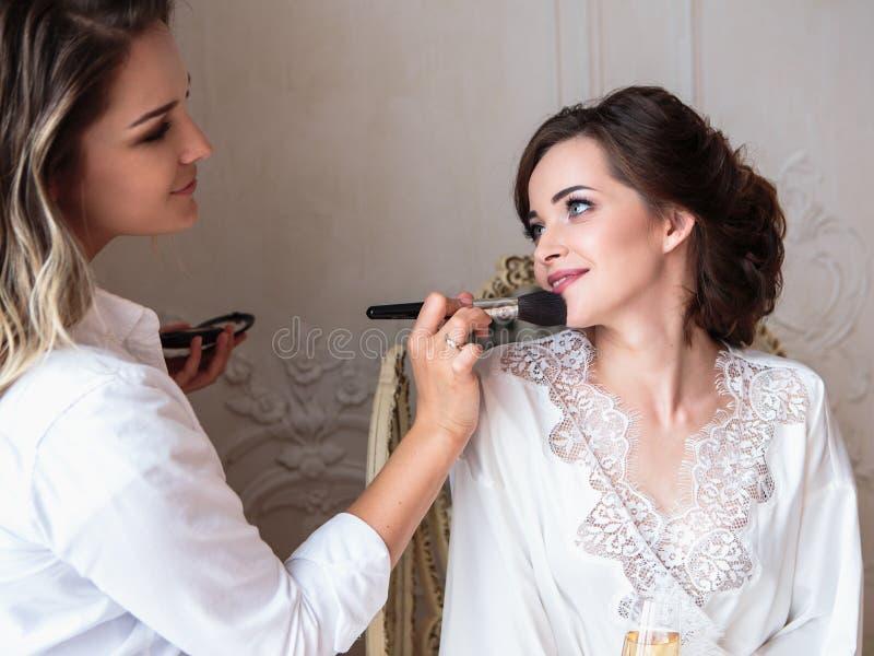 Makeupkonstnär som förbereder den härliga bruden för bröllopet i en morgon royaltyfri foto