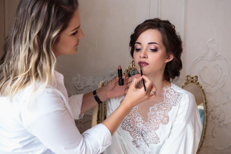 Makeupkonstnär som förbereder den härliga bruden för bröllopet i en morgon fotografering för bildbyråer
