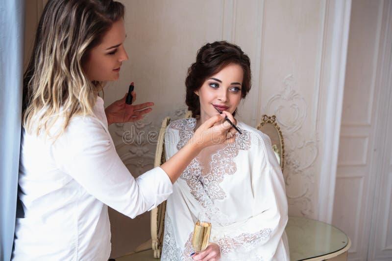 Makeupkonstnär som förbereder den härliga bruden för bröllopet i en morgon royaltyfri fotografi