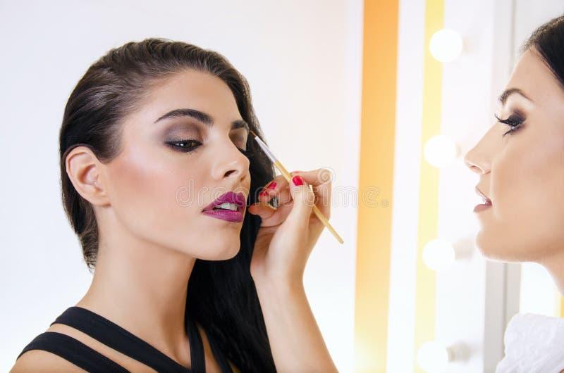 Makeupkonstnär som formar ögonbryn till den härliga flickan fotografering för bildbyråer