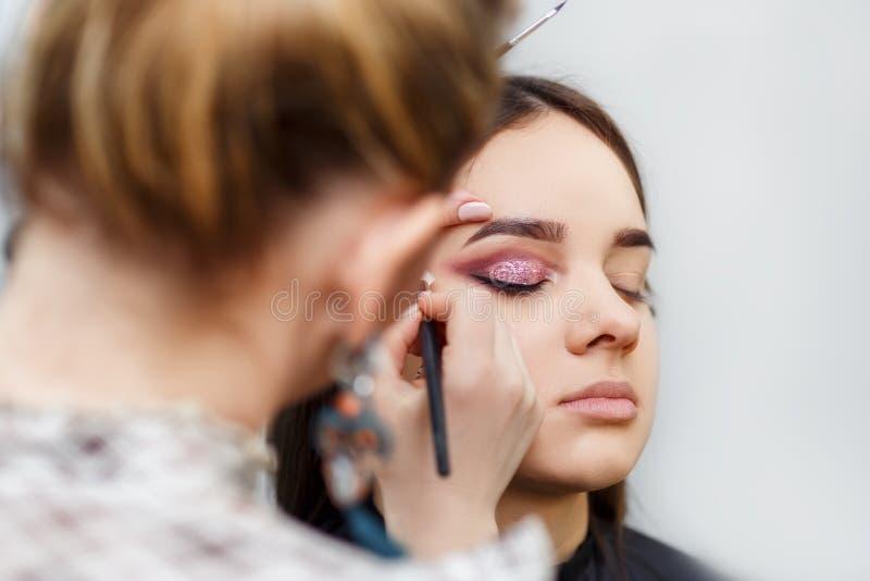 Makeupkonstnär som gör glamourmakeup arkivfoto