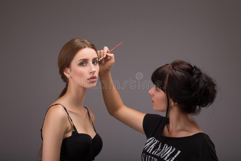 Makeupkonstnär som gör makeup för modeller för en fotofors arkivbilder