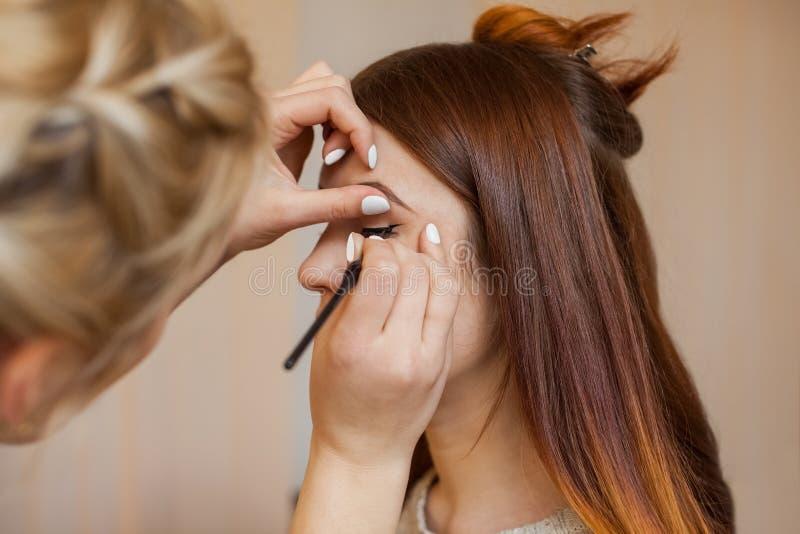 Makeupkonstnären applicerar makeup och gör ögoneyeliner med en yrkesmässig borste i en skönhetsalong royaltyfri fotografi