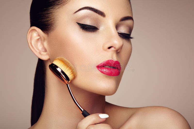 Makeupkonstnären applicerar skintone med borsten royaltyfri fotografi