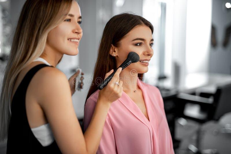 Makeupkonstnären appllying pulver på framsida royaltyfria bilder
