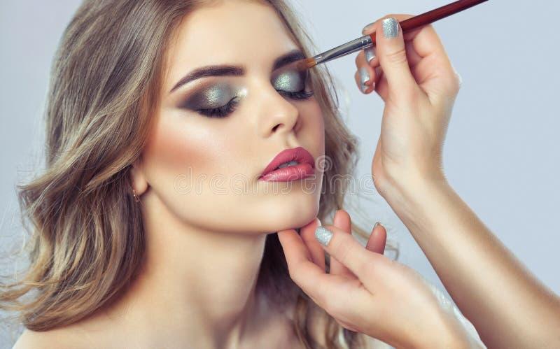 Makeupkonstnären gör rökig ögonmakeup applicera smink royaltyfria foton