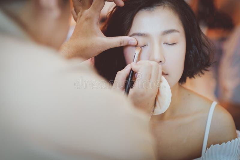 Makeupkonstn?r som applicerar rosa ?gonskugga till den h?rliga asiatiska modellen arkivfoto