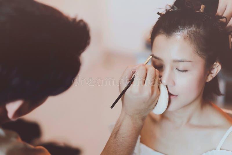 Makeupkonstn?r som arbetar p? h?rlig asiatisk modell royaltyfria foton