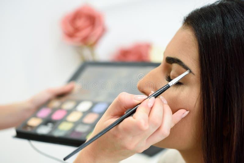Makeupkonstn?r som s?tter smink p? ?gonbryn f?r kvinna` ett s arkivfoton