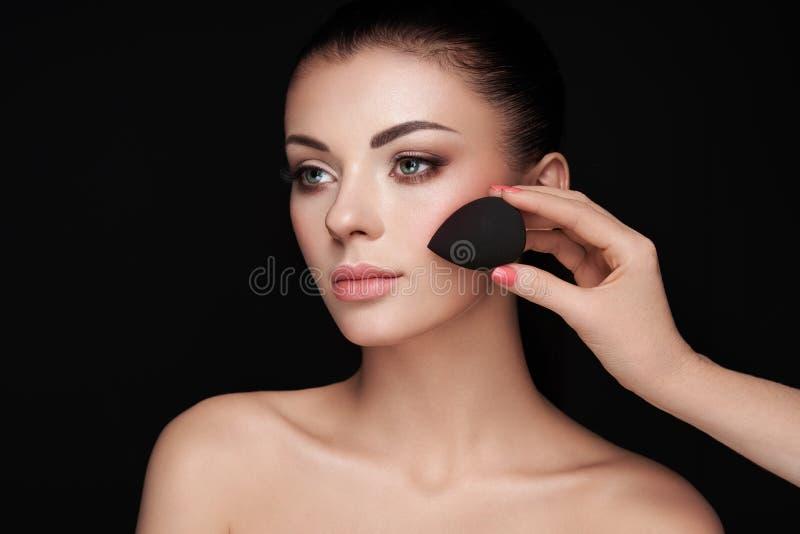 Makeupkonstn?ren applicerar skintone royaltyfri fotografi
