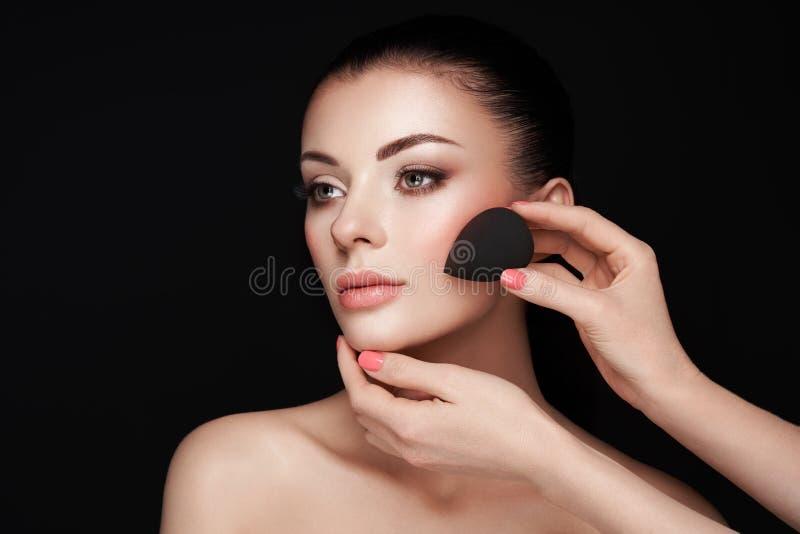 Makeupkonstn?ren applicerar skintone fotografering för bildbyråer