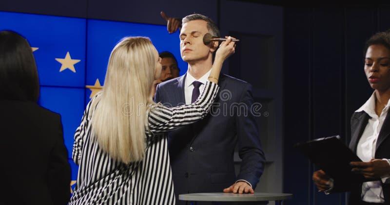 Makeupmän som förbereder politikern för meddelande royaltyfria foton