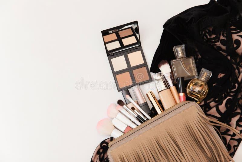Makeupp?se med kosmetiska sk?nhetsprodukter Sk?nhet och modebegrepp Kosmetiska produkter som fl?dar fr?n makeupp?se p? den vita b royaltyfri fotografi