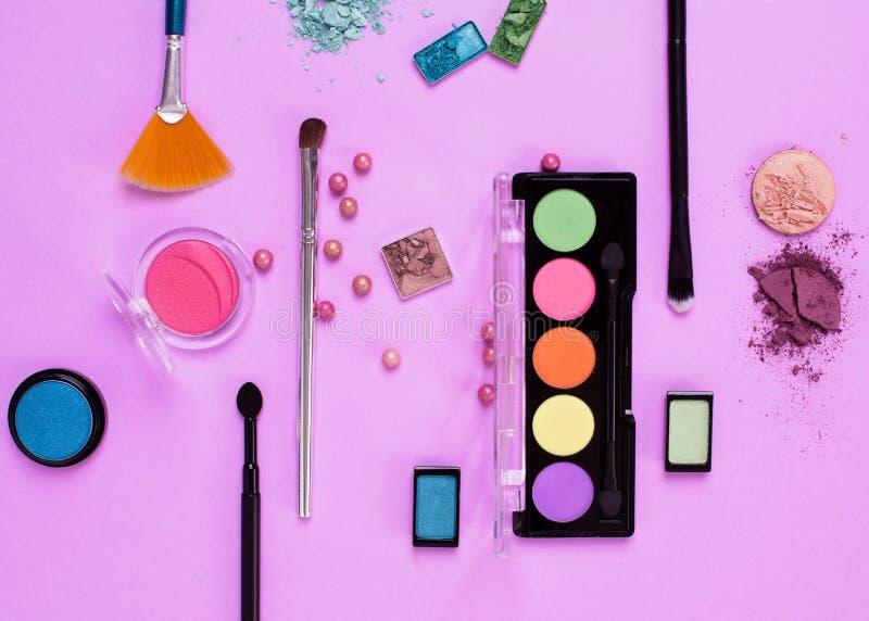 Makeupskönhetsmedel, borstar och skuggar på rosa bakgrund arkivfoto