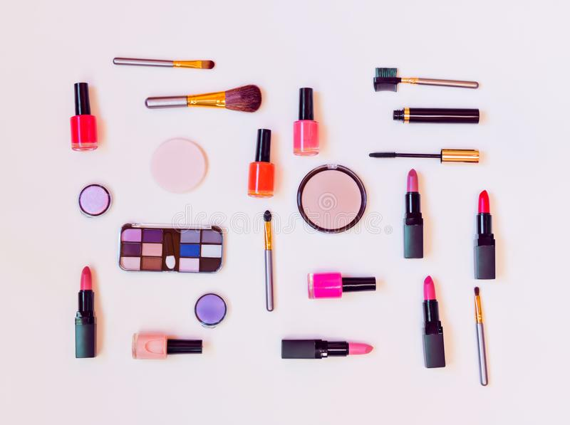 Makeupskönhetsmedel och borstar på pastellfärgad bakgrund arkivfoton