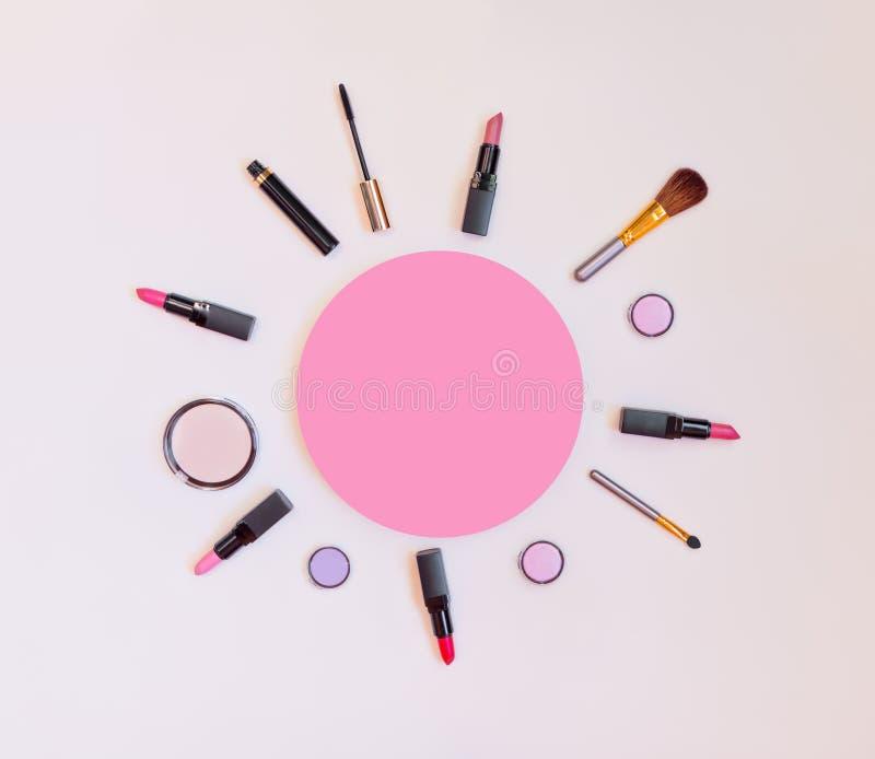 Makeupskönhetsmedel och borstar på pastellfärgad bakgrund arkivbilder