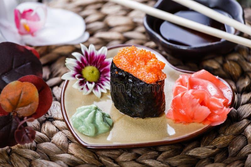 Maki de Gunkan do sushi com o caviar salmon na placa sob a forma do coração na esteira de bambu, foco seletivo fotos de stock