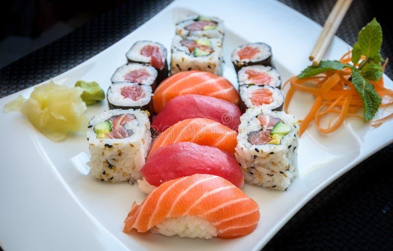 Maki dei sushi e rotolo di California con lo zenzero ed il wasabi su un piatto con i bastoncini immagini stock libere da diritti